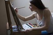 Side view of a young woman painting on easel
