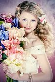 Beautiful tender girl in white festive dress holds bouquet of flowers. Over pink background.