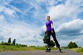 Urban sports - woman skating with Roller blades for better fitness in the city park on a cloudy summ