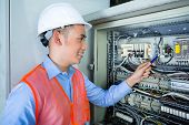 Asian Indonesian Technician or electrician making function test on breaker box or switchbox with pow