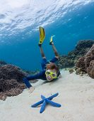 Young woman exploring sandy sea bottom and watching the blue sea star