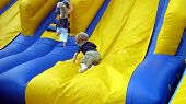 picture of inflatable slide  - boy and girl playing on an inflatable slide.
