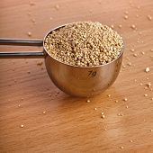 Dry yeast heap in metal scoop on wooden board table