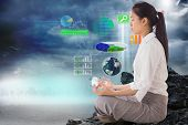 Businesswoman sitting in lotus pose against global technology background, elements of this image fur