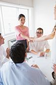 Businesswomen shaking hands at conference table during meeting in office