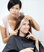 Hair stylist tries lock of dyed blond hair on the client sitting on the chair in the hairdressing salon