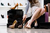 stock photo of boutique  - Female legs and variety of shoes in the footwear shop - JPG
