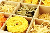 Nine types of pasta in wooden box sections close-up