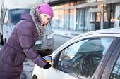 stock photo of ice-scraper  - Woman in winter clothes cleaning car windows and mirrors before the trip - JPG