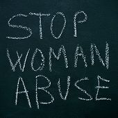sentence stop woman abuse written with chalk on a chalkboard