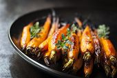 Oven baked baby carrots with thyme, in black plate over slate.