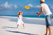 image of frisbee  - Father and daughter playing frisbee at beach - JPG