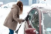 Woman with long hair cleaning car after blizzard