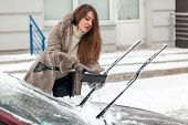 woman cleaning car with brush after blizzard