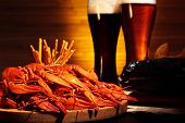 stock photo of carapace  - Glasses of dark and light beer with crawfish and smoked fish