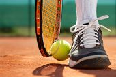 Legs of sportive man  near the tennis racquet and balls