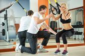 Woman doing workout with fitness straps under supervision an personal trainer