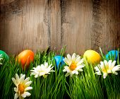 Easter. Colorful Easter Painted Eggs in Spring Grass and Flowers over Wooden Background. Easter over wood