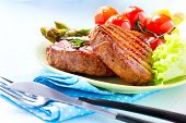 Steak. Grilled Beef Steak Meat with Vegetables - Asparagus, Cherry Tomato and Lettuce. Steak Dinner.