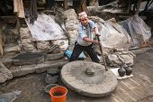 BHAKTAPUR, NEPAL - DEC 7, 2013: Unidentified Nepalese man working in his pottery workshop. More 100