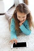Child playing on tablet pc on a carpet at home