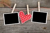 Two blank instant photos and red heart hanging. On wooden background