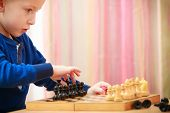 Childhood. Intelligent Boy Child Kid Playing Chess. At Home.