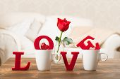 stock photo of single white rose  - Red love letters in teacups with red rose in vase for Valentine - JPG
