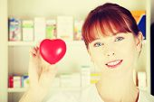 Woman in pharmacist uniform is standing in drugstore and showing red small heart, symbol of cardiolo