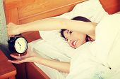 Sleepy woman in morning trying to turn off alarm clock