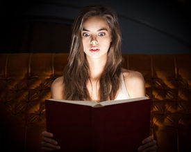 image of shock awe  - Gorgeous shocked looking young brunette woman reading book in creative lighting - JPG