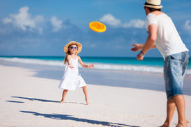 stock photo of frisbee  - Father and daughter playing frisbee at beach - JPG