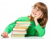 Young girl is daydreaming while reading book and wearing glasses, isolated over white
