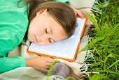 Little girl is sleeping on her book outdoors