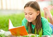 Cute little girl is reading a book while sitting on green grass