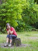 pic of pain-tree  - older woman sitting on a tree stump and looking sad - JPG