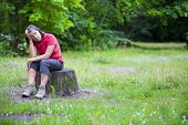 foto of pain-tree  - older woman sitting on a tree stump and looking sad - JPG