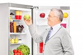 Senior man taking an apple from a refrigerator isolated on white background