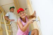 Active seniors painting wall