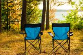stock photo of lawn chair  - two empty blue chairs for camping looking towards the river - JPG