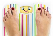 Feet On Bathroom Scale With Overwhelmed Cute Face On Dial