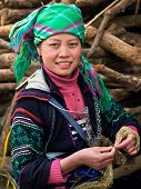 stock photo of traditional attire  - Black Hmong woman dressed in traditional attire and working with thread at Ta Van village near Sapa North Vietnam.