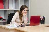 Smiling Girl Views A Page On Social Networks In Office