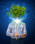 Man hold tablet pc. Green tree instead his head