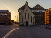 Gloucester warehouse with church at sunset