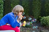 Young girl blowing bubbles from soapy water