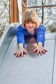 Young girl lying forward on slide