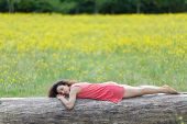 Beautiful young woman sleeping on a log or tree trunk in a rural field full of colorful yellow summe