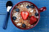 High angle photo of a large mug filled with a healthy whole grain cereal and fruit. Strawberries, bl