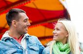 leisure, amusement park and friendship concept - smiling couple in amusement park with carousel on the back